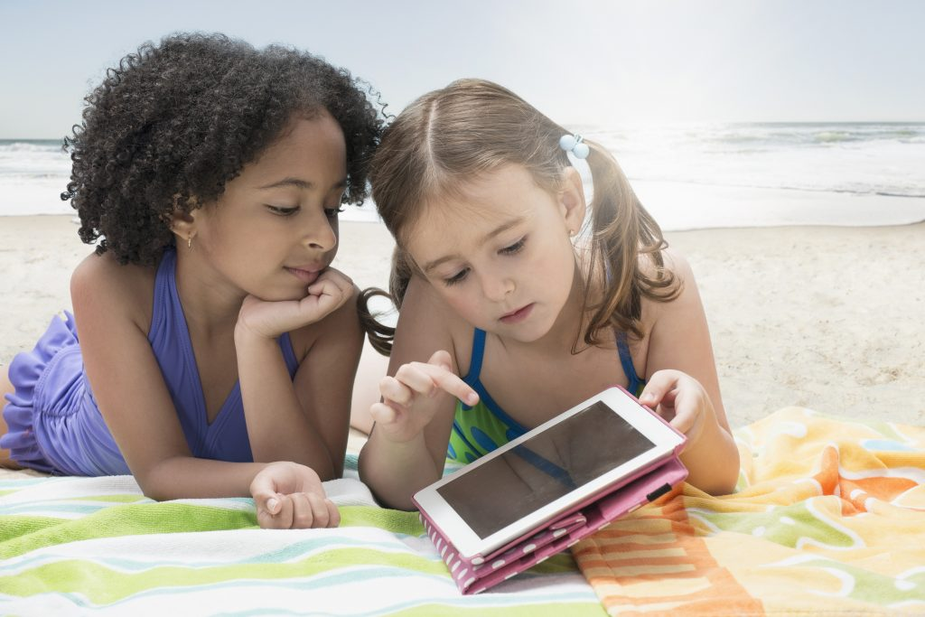 Girls using digital tablet on blanket at beach